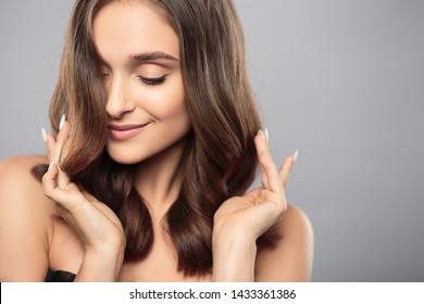Brunette Mädchen mit gesundem, lockiges Haar und natürlichem Make-up . Schöne Modellfrau mit starker Frisur. Pflege und Schönheit