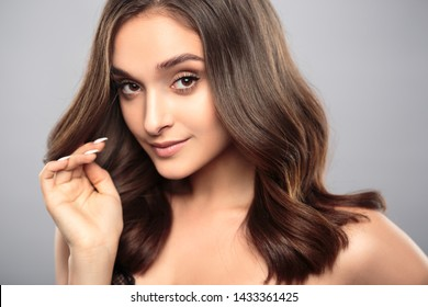 Brunette girl with healthy curly hair and natural make up . Beautiful model woman with wavy hairstyle .Care and beauty