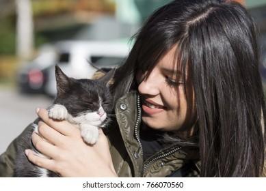 brunette girl holding black kitten