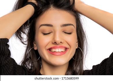 Brunette girl holding her black hair isolated on white background. Portrait of beauty girl.