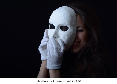 brunette girl is holding a theatrical mask near the face