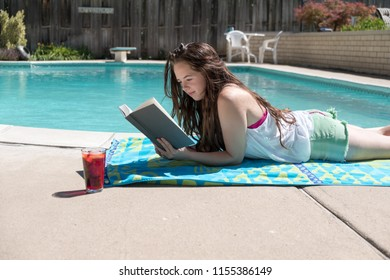Brunette girl laying on her stomach in shorts and tank top reading a novel next the swimming pool in a backyard.  Caucasian woman reading outside next to the outdoor swimming pool.