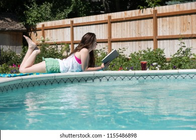 Brunette girl laying on her stomach reading a novel next the swimming pool in her backyard.  Caucasian woman reading outside next to the pool, relaxing in the summer sun.