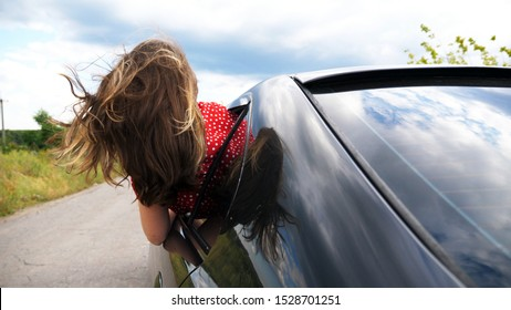Brunette girl leaning out of car window and enjoying trip while riding through country road. Young woman sticking her head out of moving auto and her long brown hair blowing in wind. Close up Slow mo