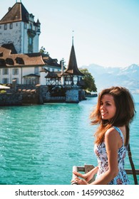 Brunette girl with long hair in a blue dress stands on the waterfront of the city of Thun, lake Geneva, transparent turquoise
