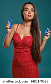 Brunette girl with a long hair, wearing a sexy red dress is holding a few gambling chips in her hands while posing against a blue background.