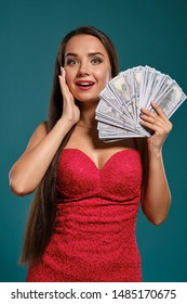 Brunette girl with a long hair, wearing a sexy red dress is posing holding a fan of hundred dollar bills against a blue background.