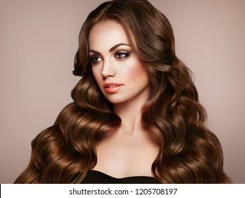 Brunette Girl with Long Healthy and Shiny Curly Hair. Care and Beauty. Beautiful Model Woman with Wavy Hairstyle. Make-Up and Black Dress - Shutterstock ID 1205708197