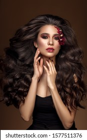 Brunette girl with long , healthy and shiny curly hair . Beautiful model woman with wavy hairstyle .Care and beauty gorgeous makeup