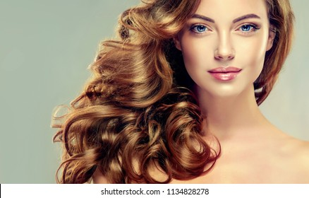 Brunette  girl with long  and   shiny curly hair .  Beautiful  model woman  with wavy hairstyle   .Care, cosmetics and beauty