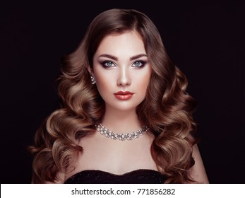 Brunette Girl with Long and shiny Curly Hair. Beautiful Model Woman with Curly Hairstyle. Care and Beauty Hair products. Perfect Make-Up and Jewelry