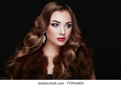 Brunette Girl with Long and shiny Curly Hair. Beautiful Model Woman in the Fur Coat Care and Beauty Hair products. Perfect Make-Up and Jewelry