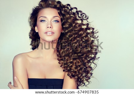 brunette girl long shiny curly hair の写真素材 今すぐ編集