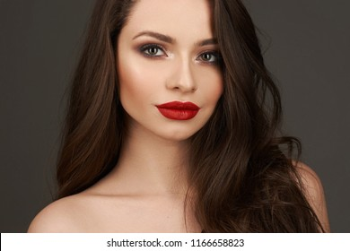 Brunette girl with long shiny wavy hair . Beautiful model with curly hairstyle and red lips. Young pretty woman looking at you or in camera