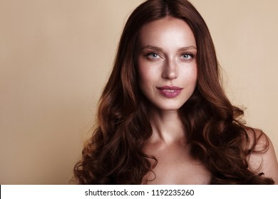 Brunette girl with long and shiny wavy hair . Beautiful model with curly hairstyle and makeup.