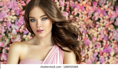 Brunette  girl with long  and   shiny wavy hair .  Beautiful  mode woman with curly hairstyle ,   background  wall of flowers . Skin Care, beauty and  spa cosmetic