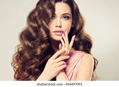 Brunette  girl with long  , shiny wavy hair .  Beautiful  model with curly hairstyle . Woman with beautiful hands  french manicure