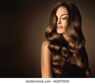 Brunette  girl with long  and   shiny wavy hair .  Beautiful  model with curly hairstyle . Head and shoulders