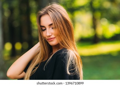 A brunette girl with a make-up looks down and holds her hand in her hair