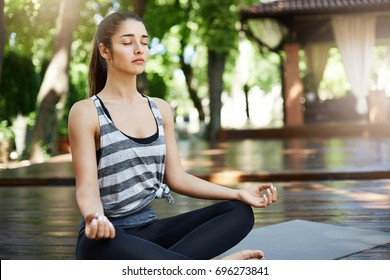Brunette girl meditating in the middle of yoga temple breathing deep searching for a relief