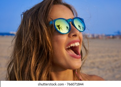 Brunette girl on beach sunglasses with palm tree reflection