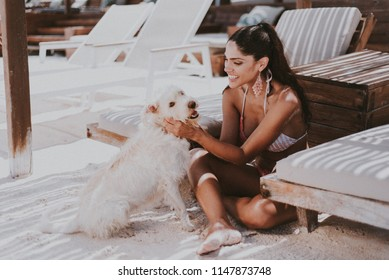 Brunette girl on a beach with a White dog