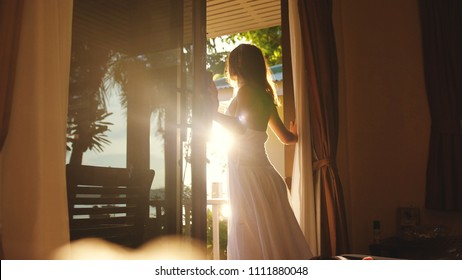 Brunette girl opens the door in the early morning during sunrise with lens flare effects