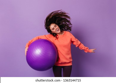 Brunette girl in orange sweatshirt plays with hair and holds purple fitball on isolated background