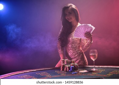 Brunette girl with a perfect hairstyle and bright make-up is posing with fan of hundred dollar bills in her hands. Casino, poker.