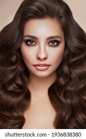 Brunette girl with perfect makeup. Smiling beautiful model woman with long curly hairstyle. Care and beauty hair products