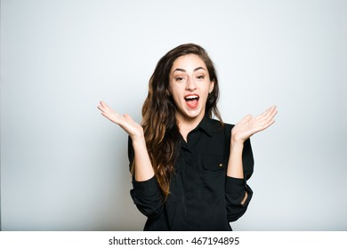 brunette girl is pleased a surprise, dressed in black, isolated on white background