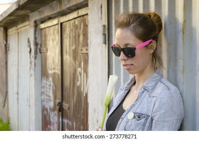 Brunette girl posing with a flower by the garage door, wearing funny sunglasses