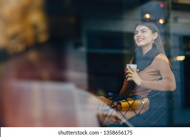 brunette girl sitting at a caffe drinking a hot beverage while looking out the window