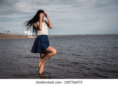 Brunette girl in a skirt standing in the water with her hair down. She against the background of concrete and hydroelectric power. dramatic light.