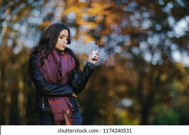 brunette girl is smoking an e-cigarette in the park drung autumn