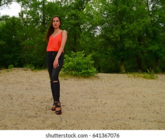 Brunette girl standing on the sand near the forest