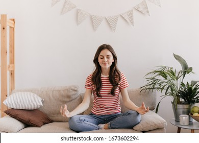 Brunette girl in striped T-shirt is meditating while sitting on sofa in living room. Calm woman in red tee relaxing on beige couch at home