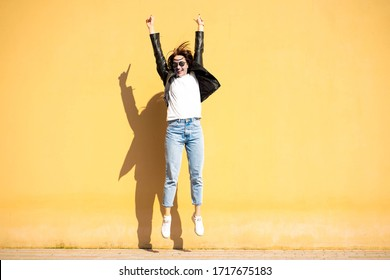 Brunette girl in a sunglasses and a casual clothing (white t shirt, blue jeans and a black jacket), is jumping and smiling in front of yellow wall. Picture with a colorful background and a copy space