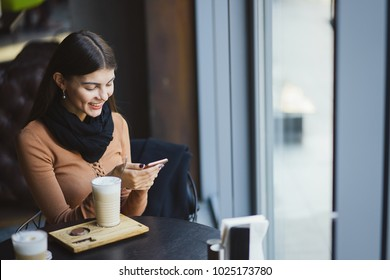 brunette girl using her phone while drinking coffee at a restaurant