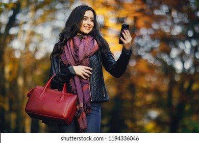 brunette girl using her phone as she is relaxing at the park during autumn