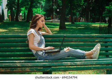 brunette girl using a laptop at the park sits on a bench