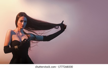 Brunette girl with very long hair on colorful background.