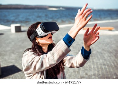 Brunette girl in virtual reality glasses have fun in the park
