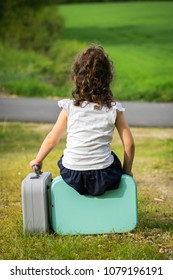 a brunette girl, waiting, sitting on a suitcase holding another in her hand