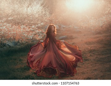 A brunette girl with wavy, thick hair runs to the sun and looks back. The princess has a luxurious, chiffon, red dress that flutters in the wind. Background of a fiery sunset and wild nature