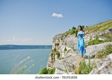 Brunette girl, wear on blue dress stands barefoot at cliff with amazing landskape.
