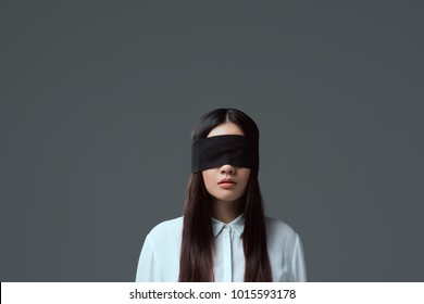 brunette girl wearing black blindfold isolated on grey