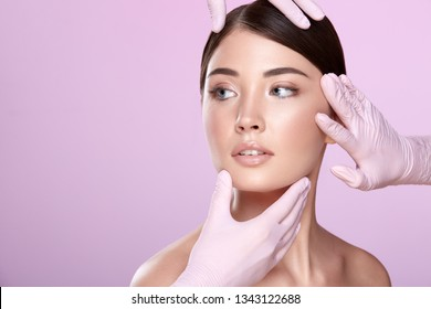 Brunette girl wearing evening nude up with long lashes posing at pink studio background. Hands in medical glove on patient's face, close up portrait.