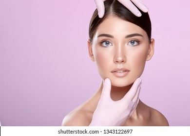 Brunette girl wearing evening nude up with long lashes posing at pink studio background. Hands in medical glove on patient's face, close up.