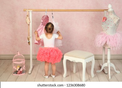 163d386e a brunette girl in a white jacket and a pink tutu skirt chooses a beautiful  dress